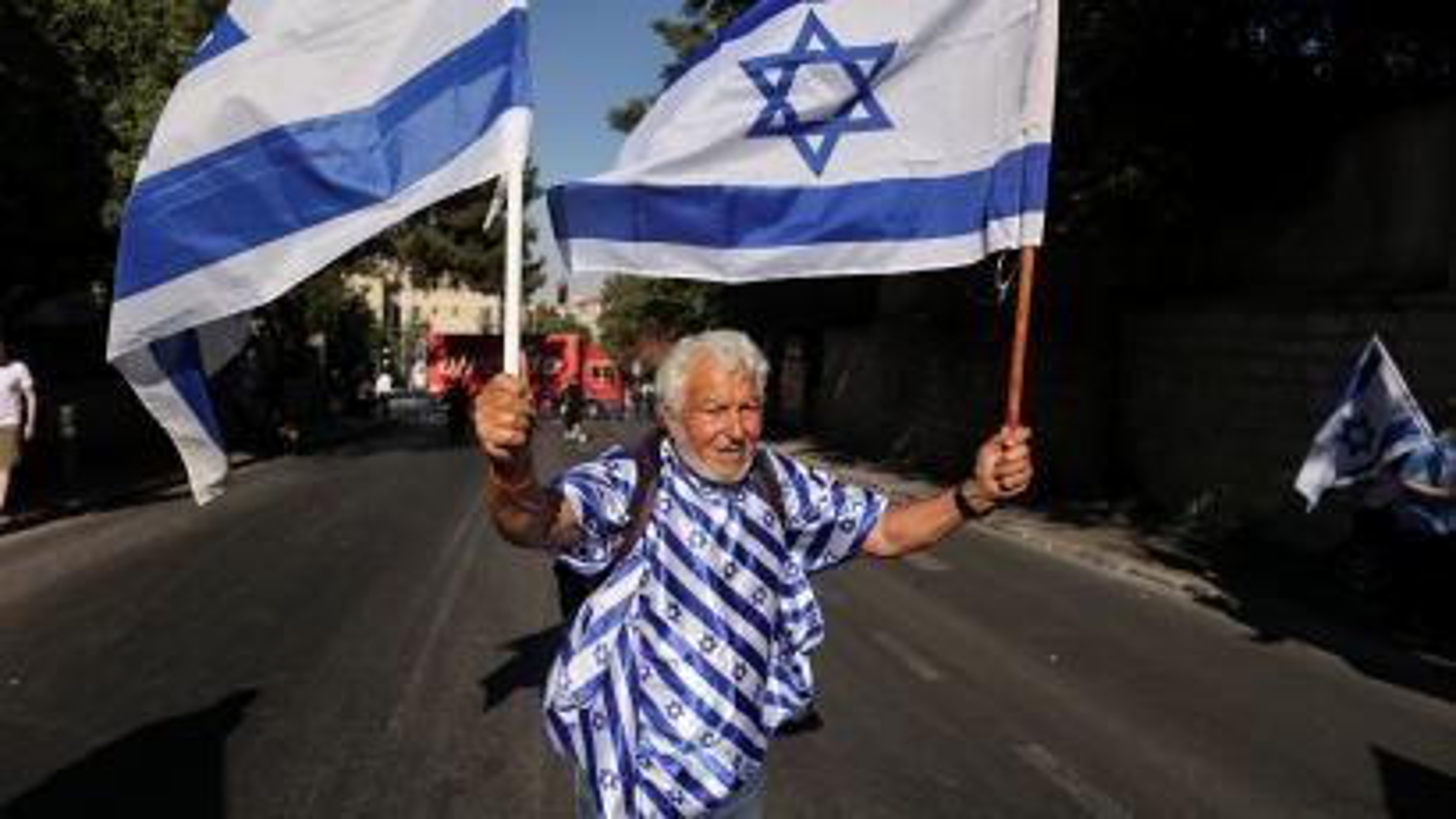 A man holds Israeli flags outside Jerusalem's Old City.