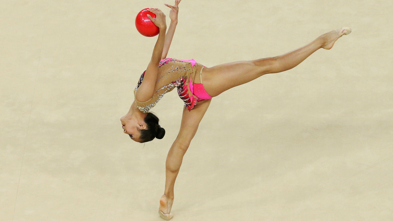 Rhythmic gymnast performs with ball.