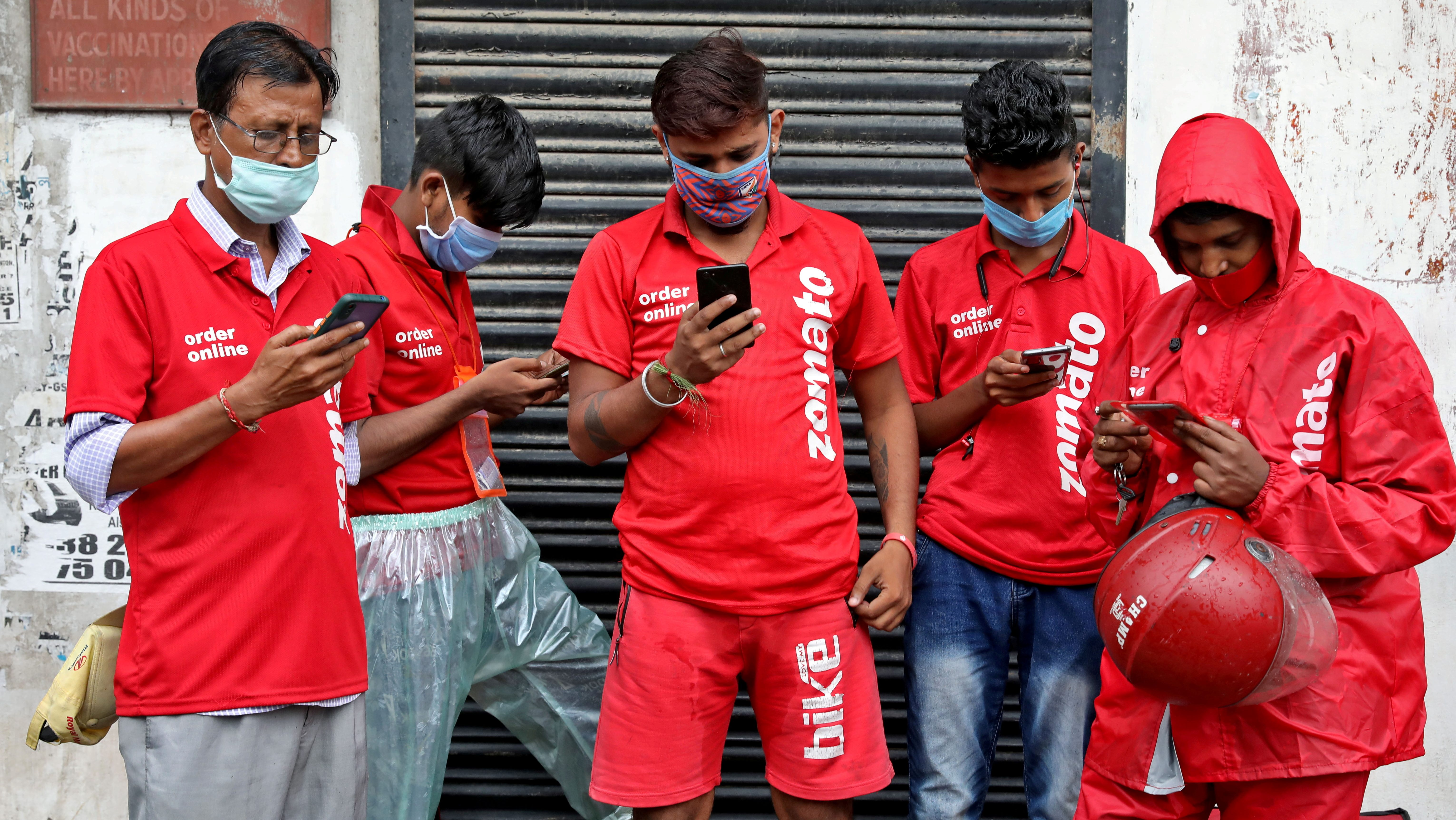 FILE PHOTO: Delivery workers of Zomato wait to collect orders outside a restaurant in Kolkata