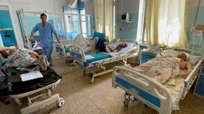 Wounded Afghan men receive treatment at a hospital after yesterday's explosions outside airport in Kabul