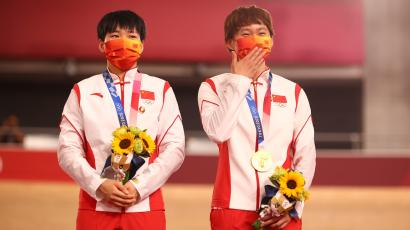 Gold medallists Bao Shanju and Zhong Tianshi wear protective face masks and pose with badges of the late Chinese chairman Mao Zedong pinned to their tracksuits