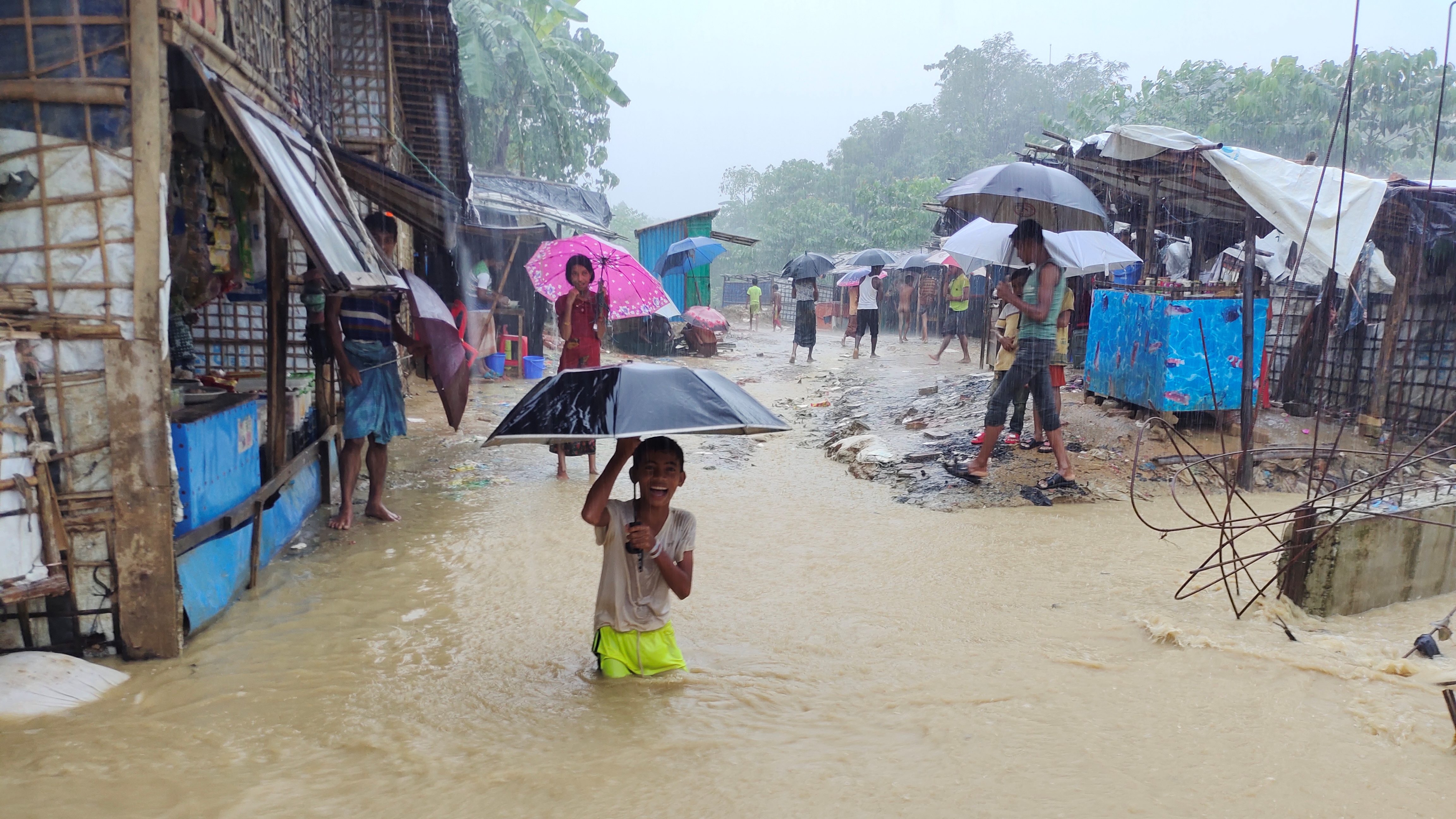 A boy plays in the flooded street after heavy monsoon rains triggered flooding at Kutapalong refugee camp in Bangladesh