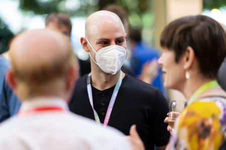 Attendees wearing face mask mingle with those without facial coverings