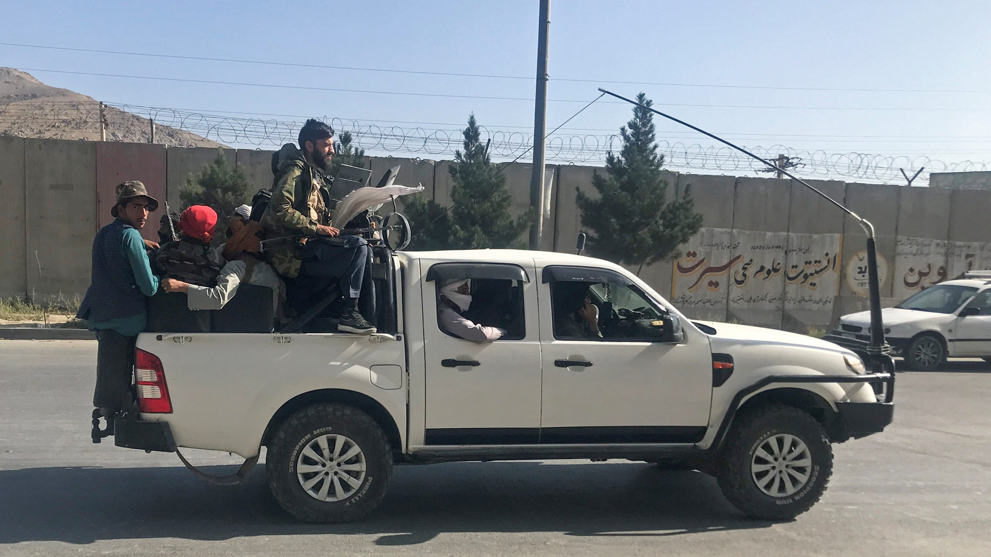 Taliban fighters ride a pick-up truck into Kabul