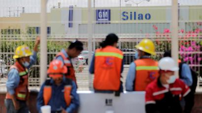 Workers wait outside the General Motors plant in Silao, Mexico.