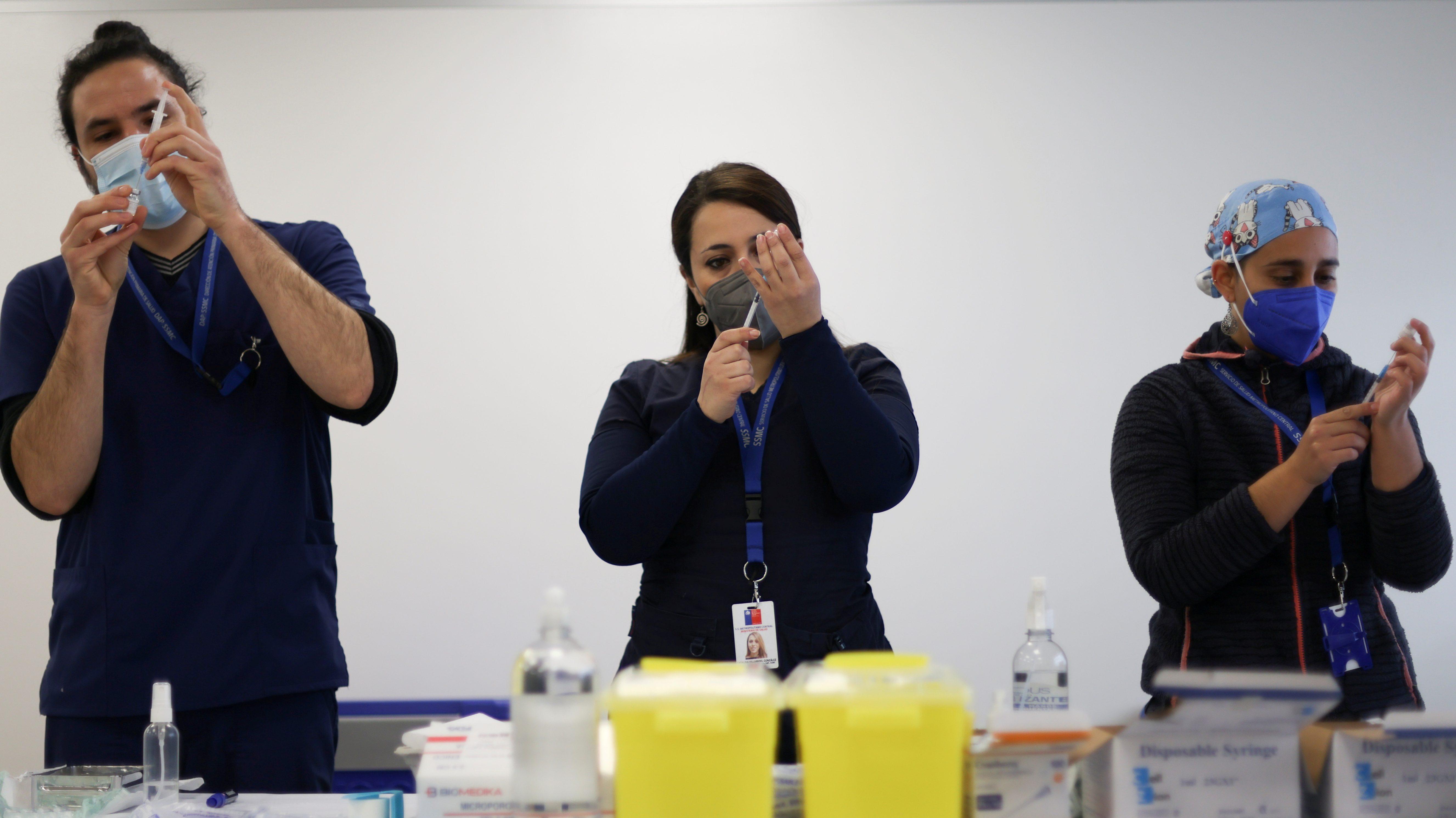 Healthcare workers prepare doses of Pfizer/BioNTech coronavirus disease (COVID-19) vaccines