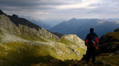 A hiker looks at a mountain range at the Hohe Tauern National Park near the village of Virgen, Austria, July 23, 2018. Picture taken July 23, 2018.
