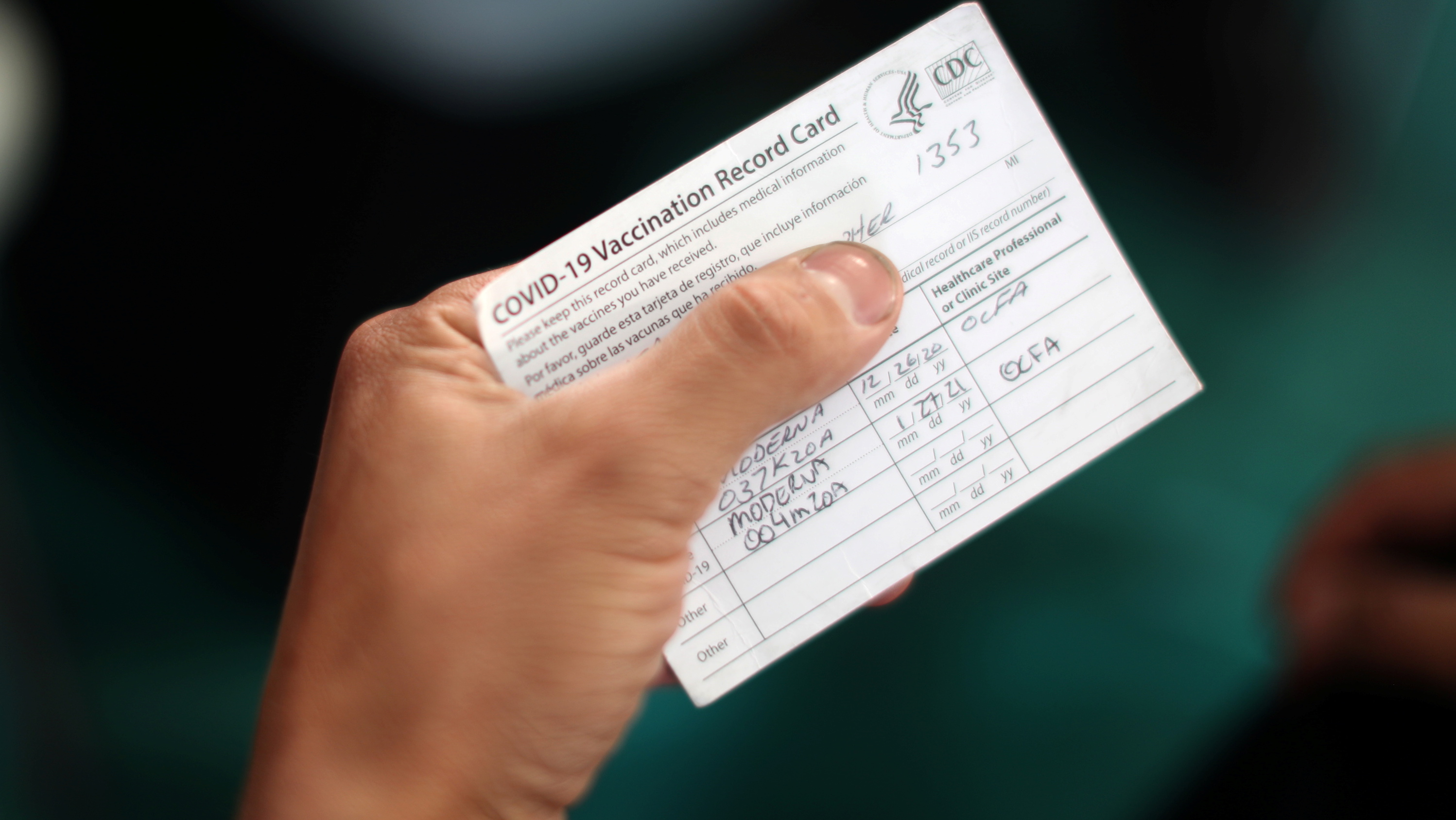 hand holding CDC covid vaccination card