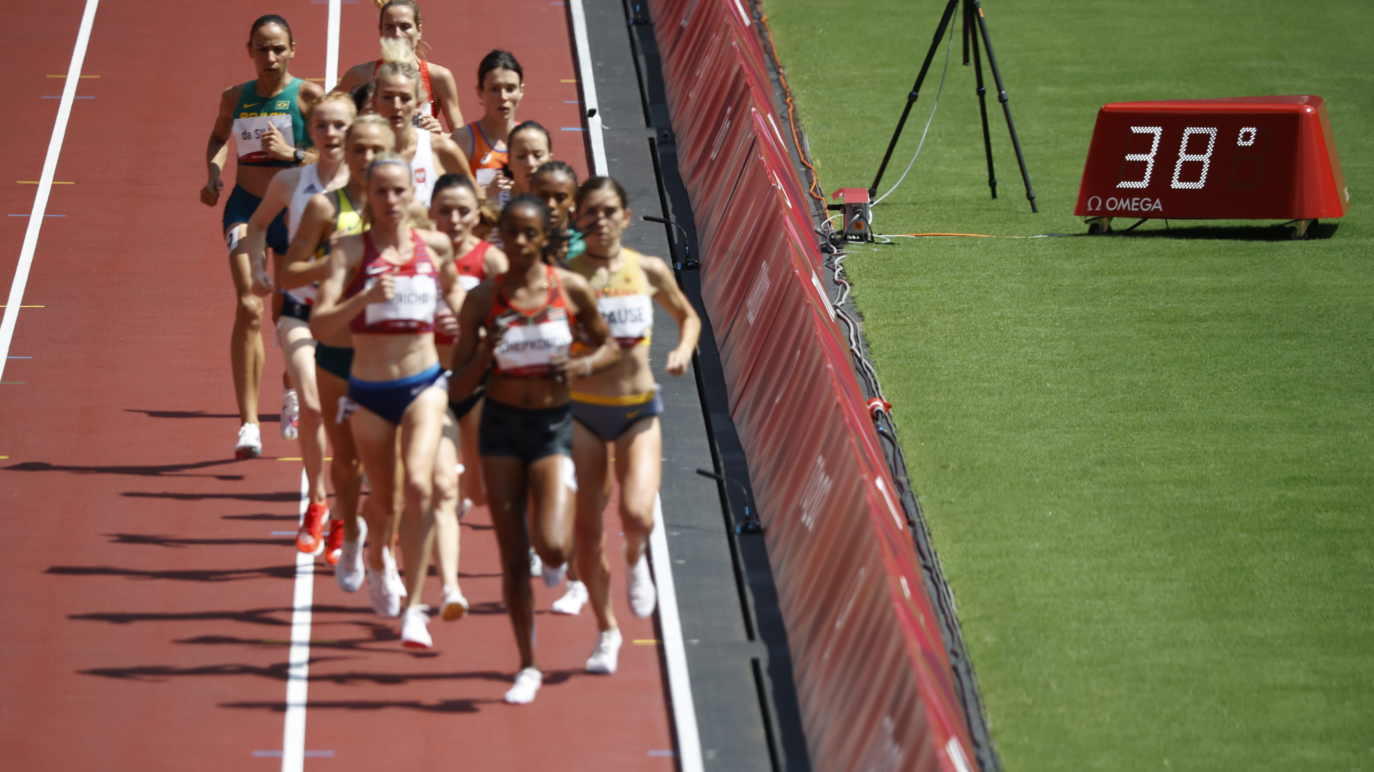 Women participate in the 3000m steeplechase beside a thermometer that lists the temperature at 38˚C (100.4˚F)