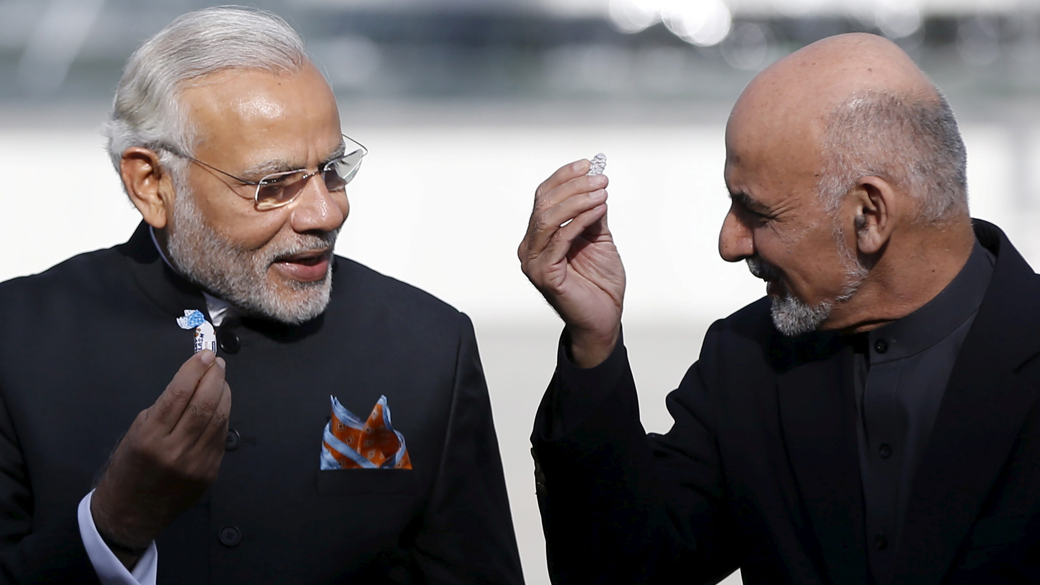 India's PM Modi and former Afghanistan's President Ashraf Ghani hold sweets as they inaugurate Afghanistan's new parliament building in Kabul Afghanistan