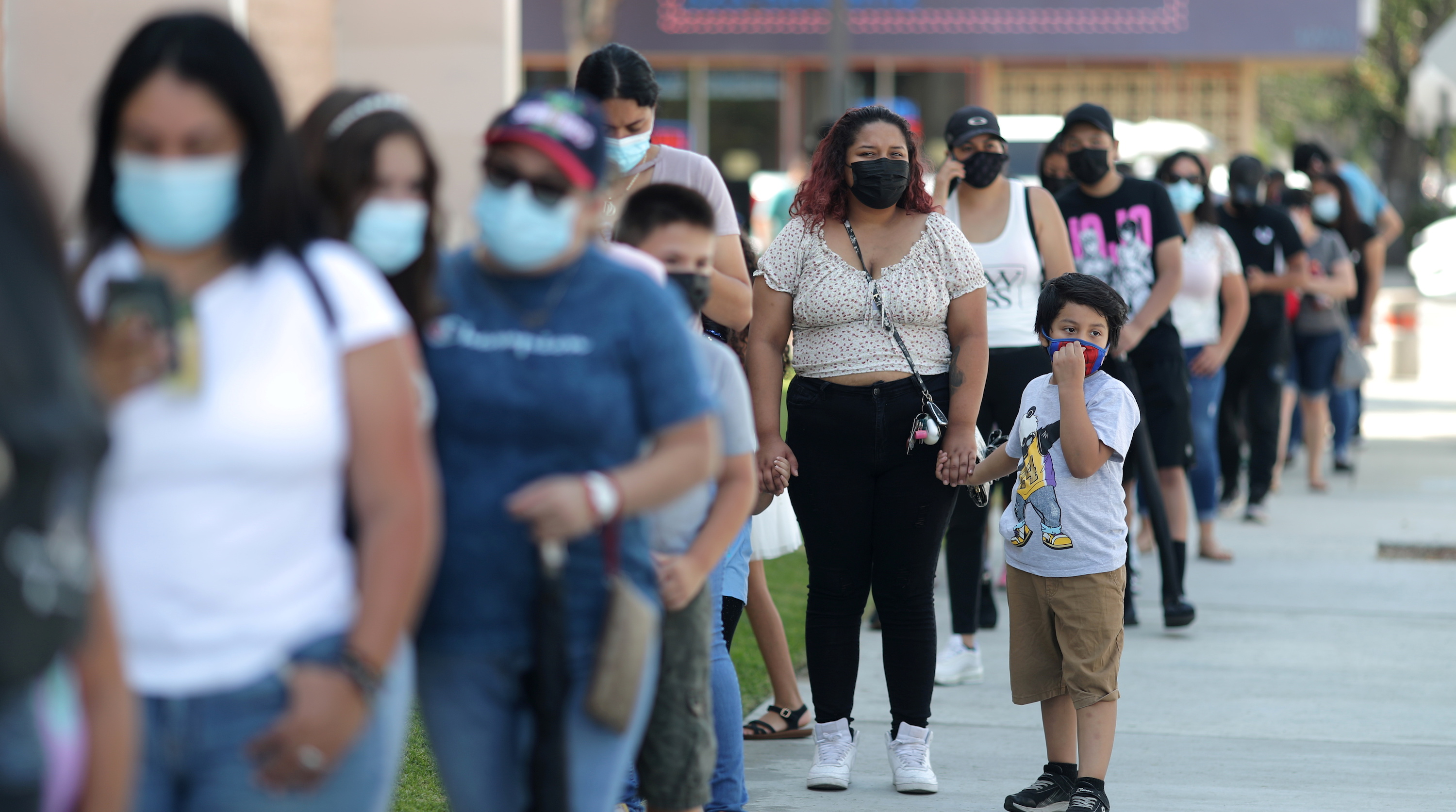 People waiting in line outside a Covid testing site wearing masks