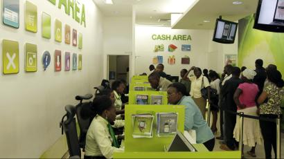An image of people in a hall that resembles a banking hall, but instead its a queue for mobile money transfers