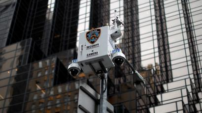 A security camera with New York Police Department logo is seen. A skyscraper is in the background.