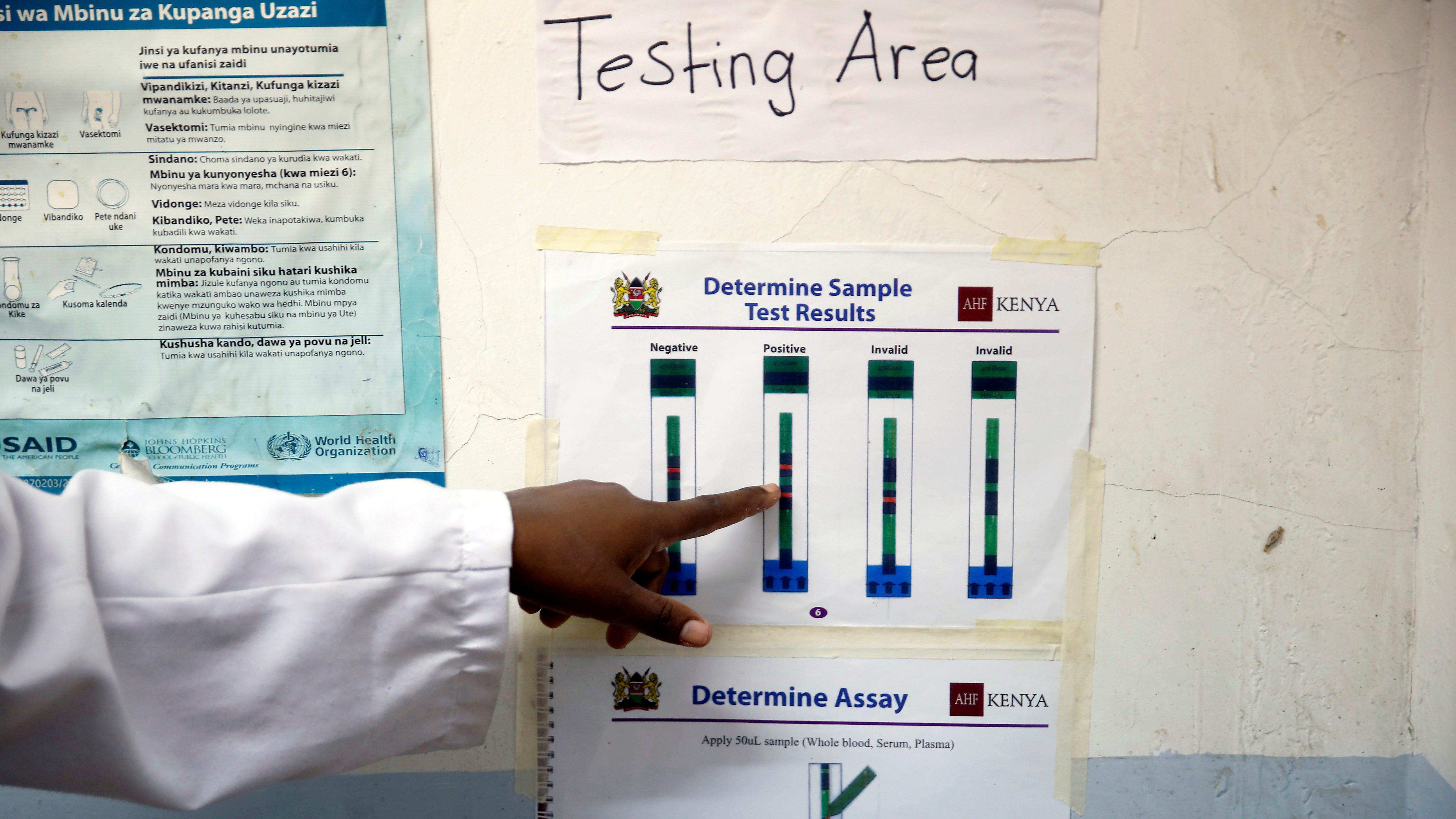 A finger points to a poster of test results.