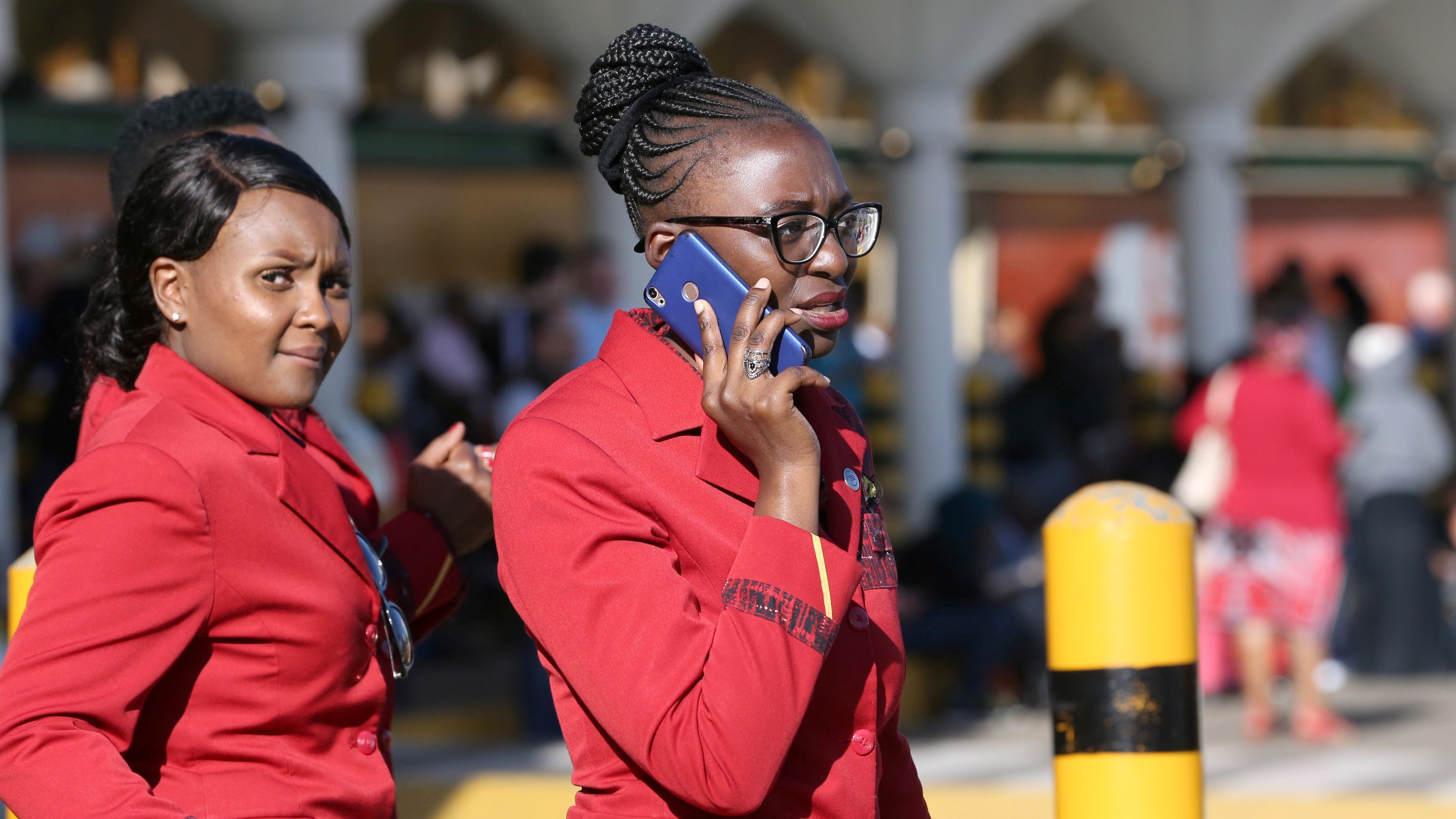 A flight attendant in red attire and glasses talks on her blue mobile phone while another one walks behind her.