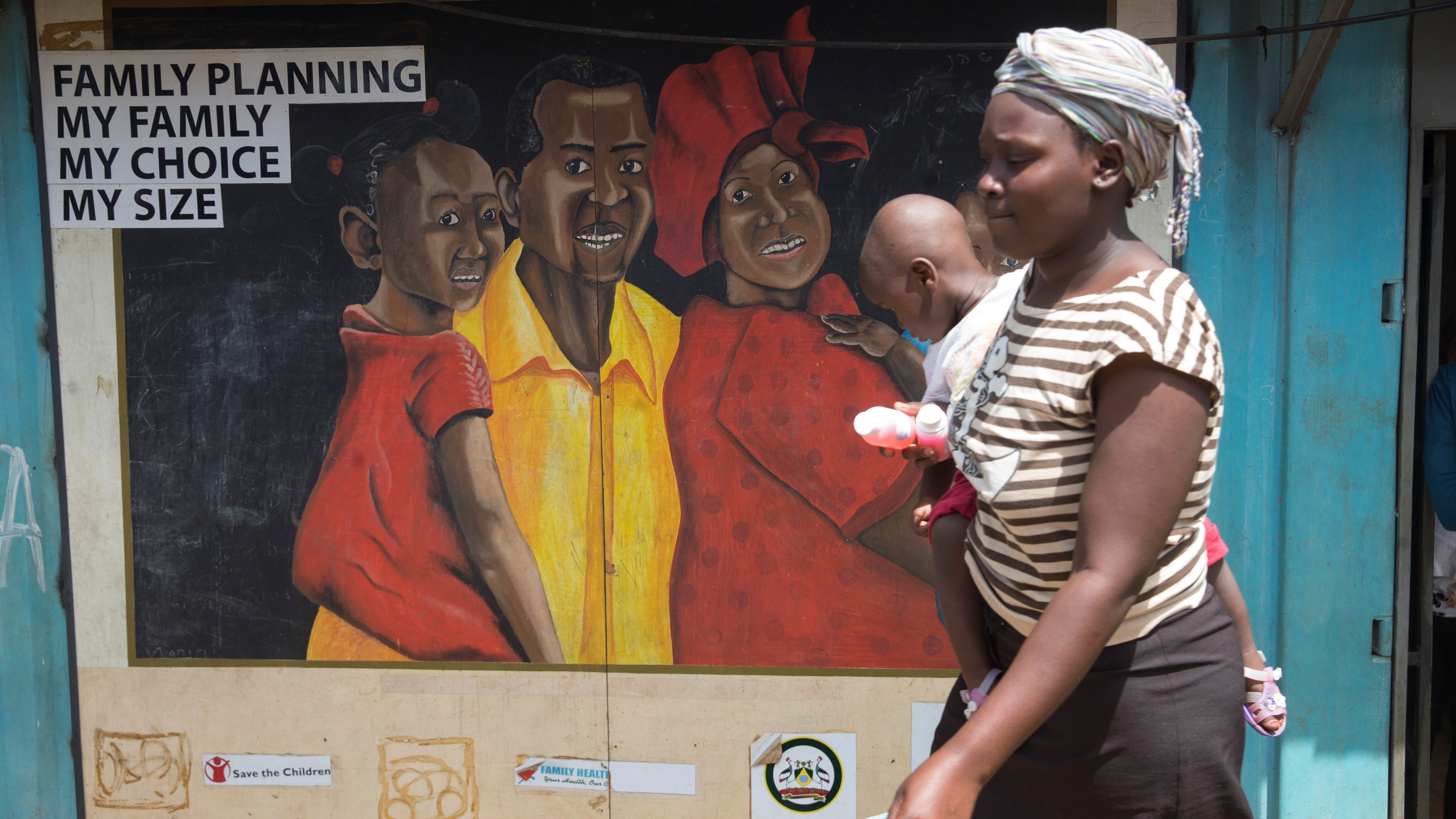 A woman carrying a baby walks past a mural showing a man, woman and child.