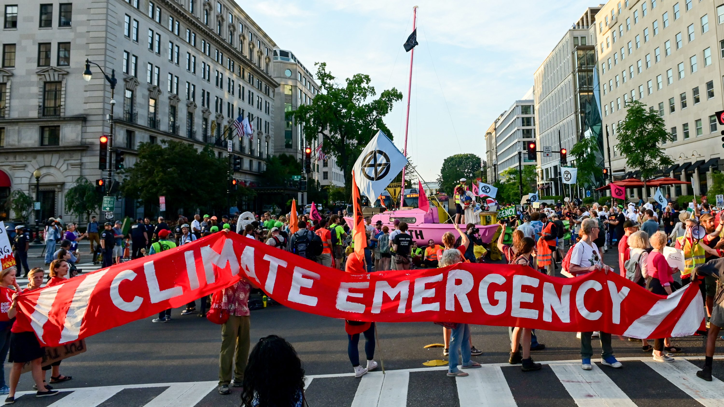 A group of protesters walk down a city street carrying a red banner that reads CLIMATE EMERGENCY