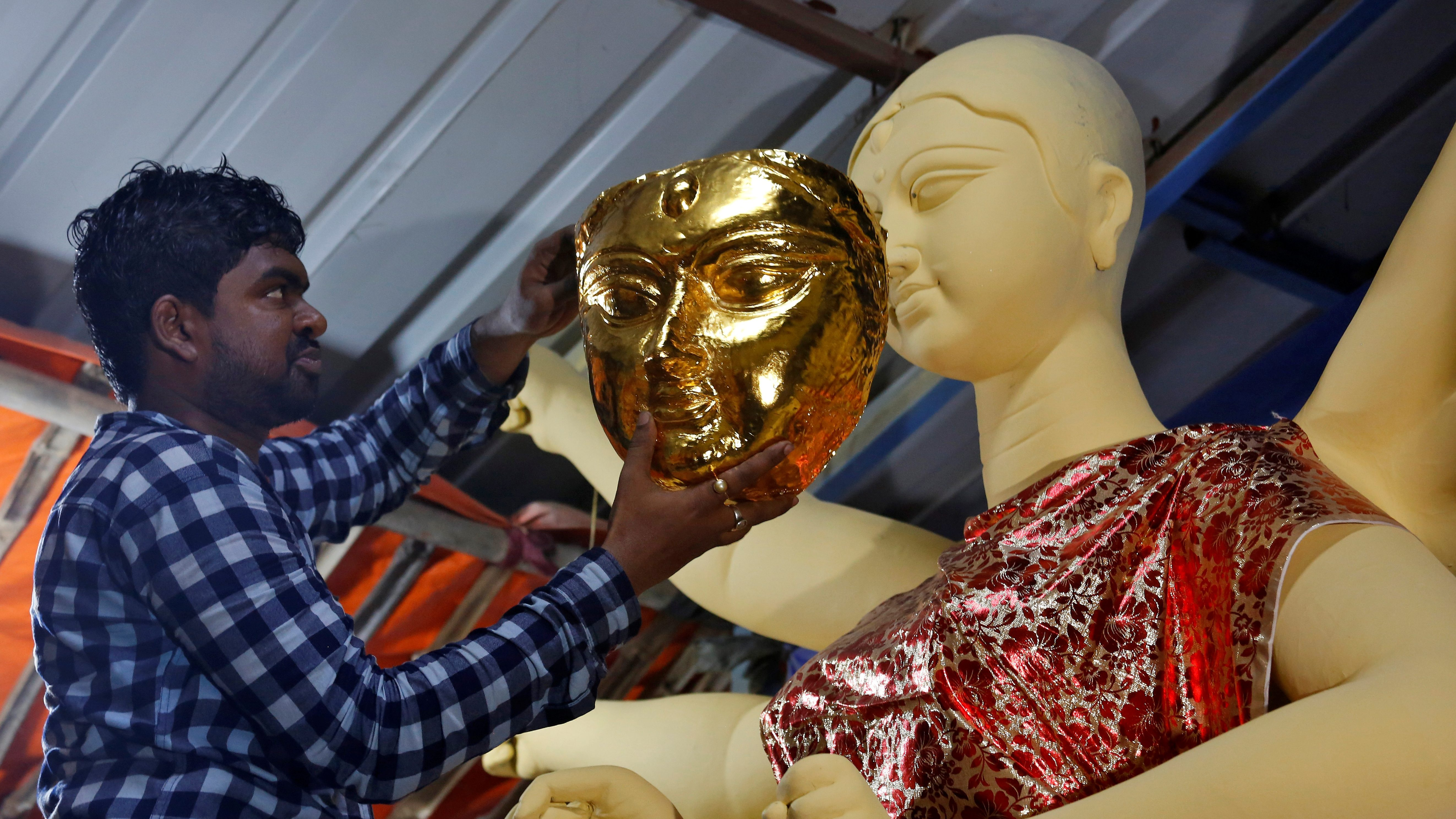 An image of an artisan tries a gold face on an idol of the Hindu goddess Durga during a media preview inside a workshop during preparations for the upcoming Durga Puja festival in Kolkata