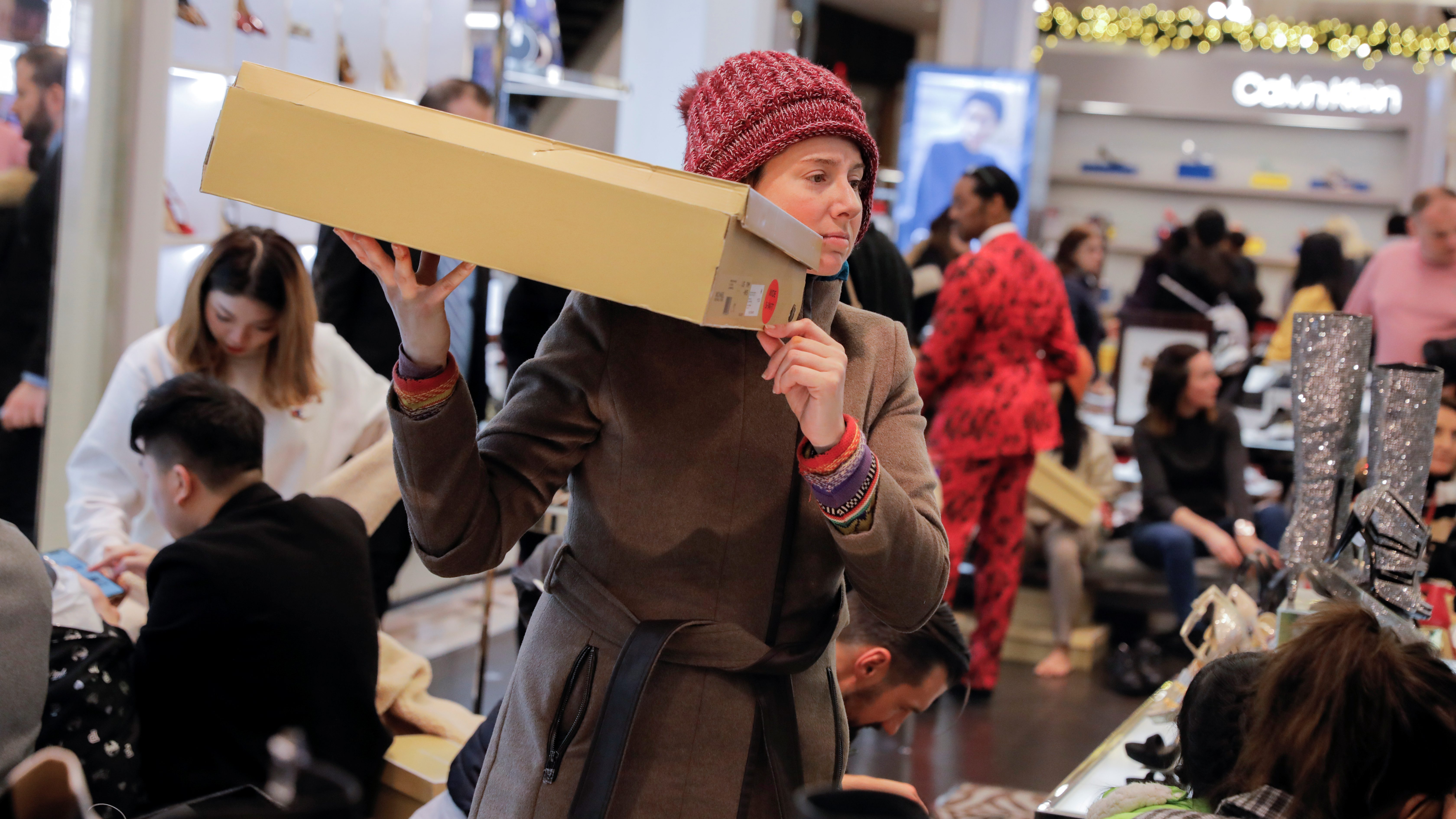 A woman holds a box aloft amid a sea of holiday shoppers at a Macy's department store.