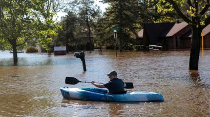 Resident Joe Ryan paddles a kayak to check on his home in a flooded neighborhood along the Tittabawassee River, after the two dam failures in Midland, Michigan, U.S., May 20, 2020.
