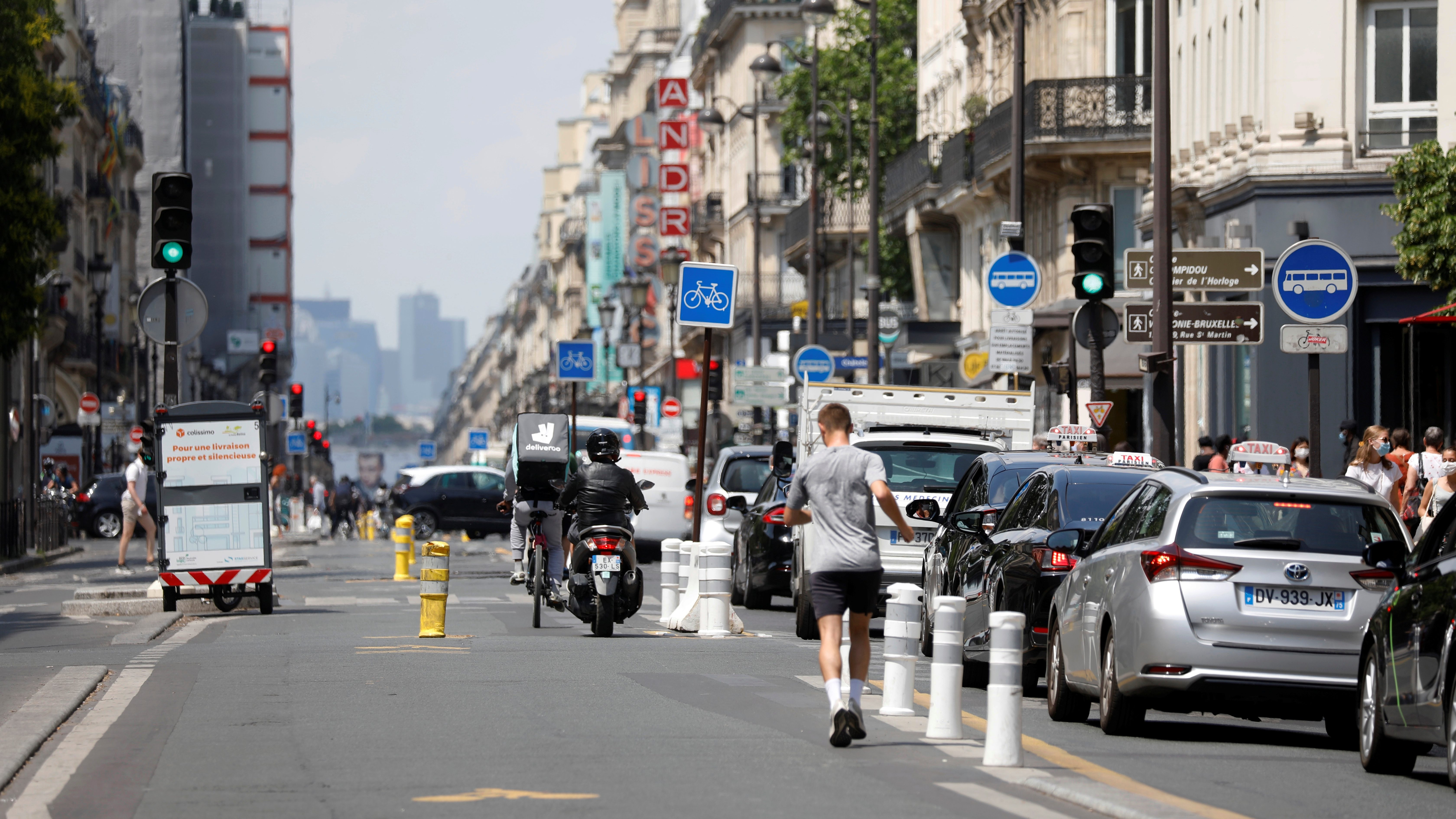 a jogger runs along a portion of a city street protected with barriers, while a line of vehicles moves on his right.
