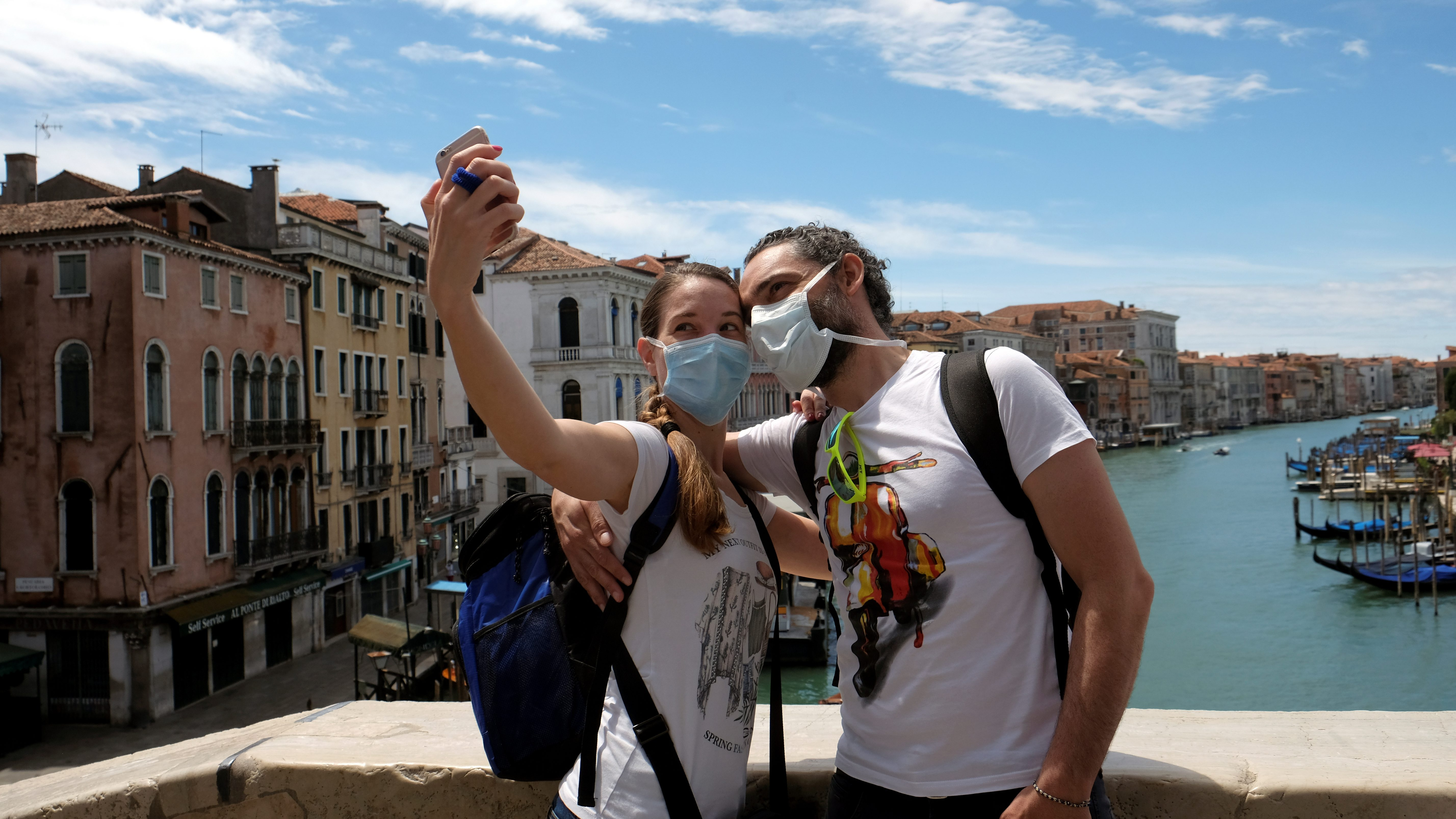 Tourists wearing protective masks take a selfie on the Rialto Bridge following the outbreak of the coronavirus disease (COVID-19) in Venice