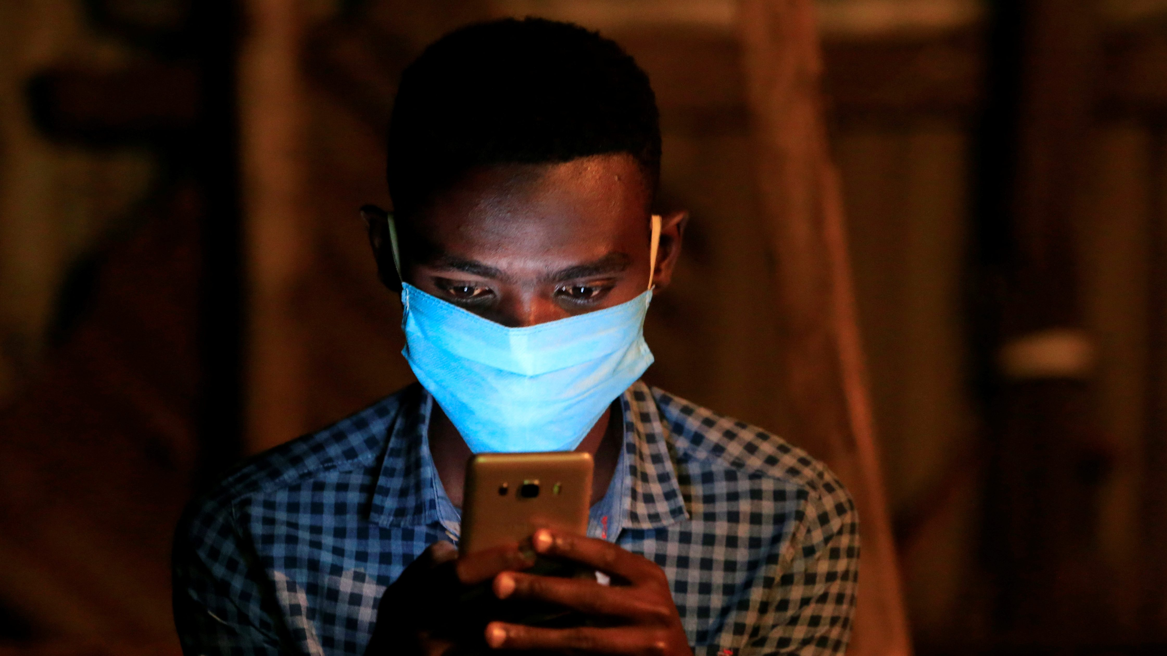 A man in a mask uses his mobile phone in a dimly lit space.