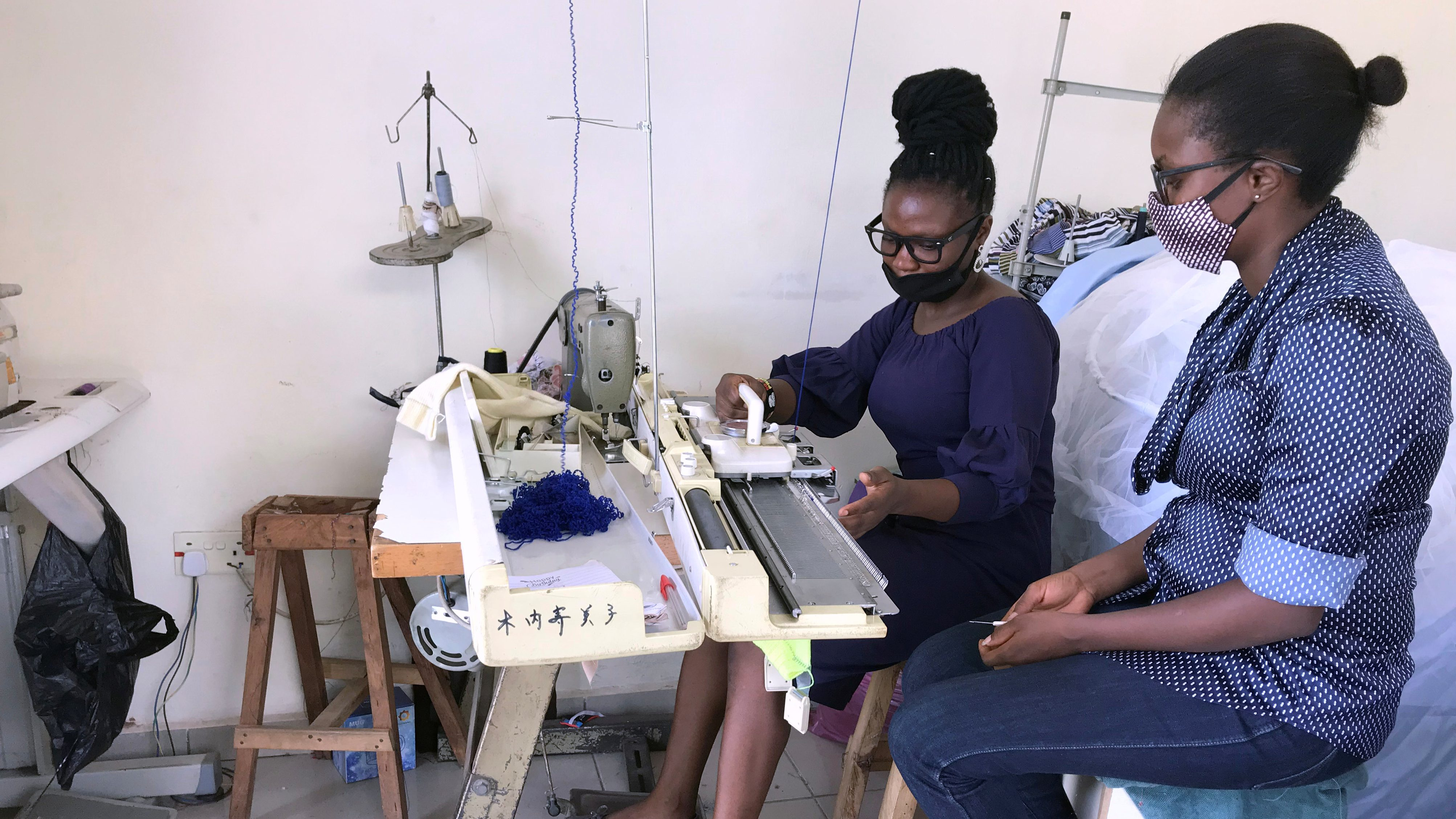 A woman learns how to use a sewing machine from another woman who watches and observes