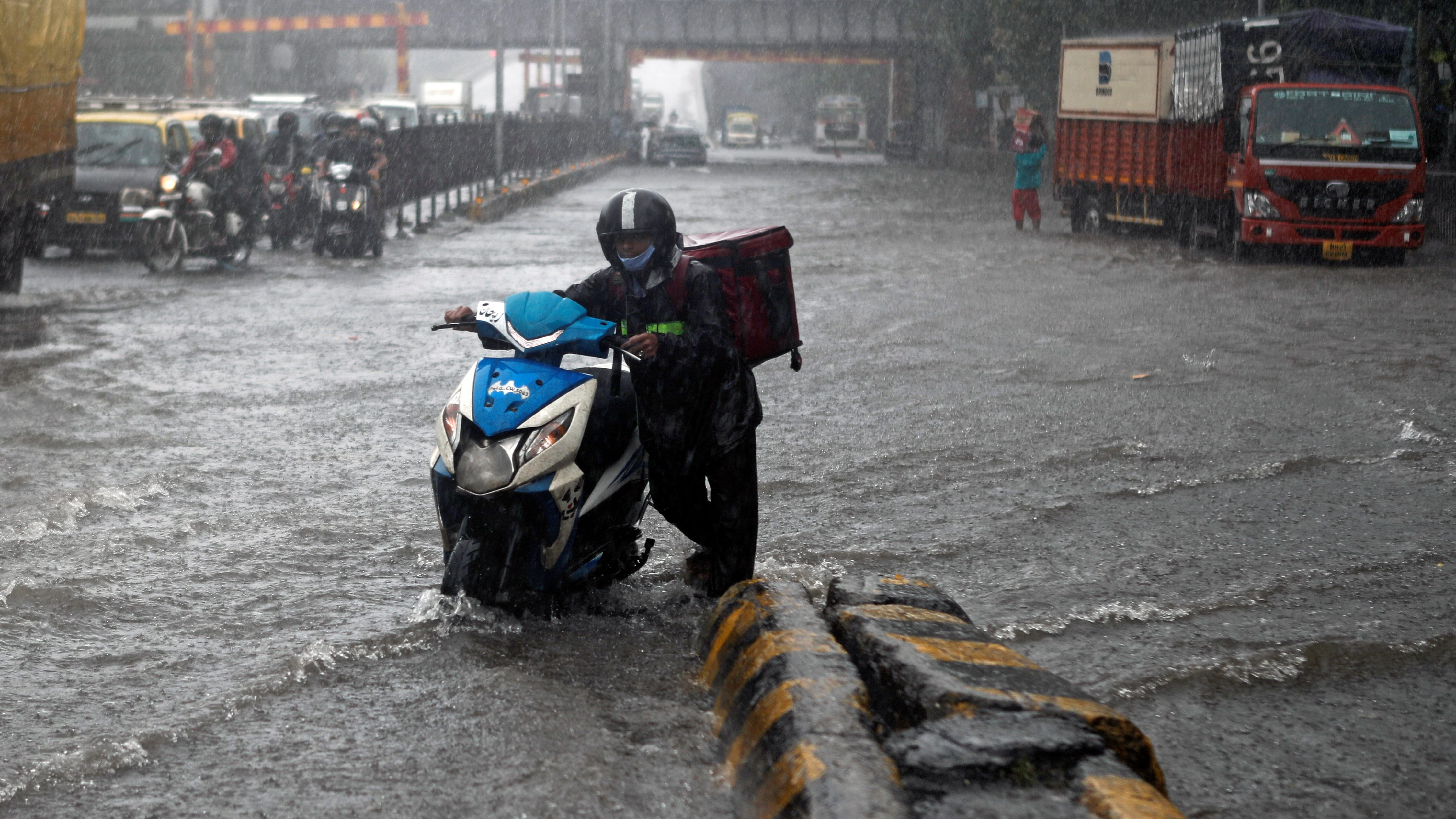 Delivery boy pushes his scooter after it stopped working along a waterlogged road following heavy rainfall in Mumbai