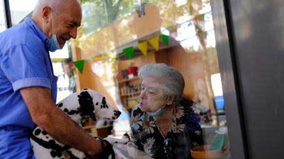 Maria de Concepcion Illa, 89, who lives in a care home, blows a kiss to Menta, the dog of her neighbour Antoni (L), 70, as they talk through a glass front at the Centre Parc nursing home after Catalonia's regional authorities announced restrictions to contain the spread of the coronavirus disease (COVID-19), in Barcelona, Spain