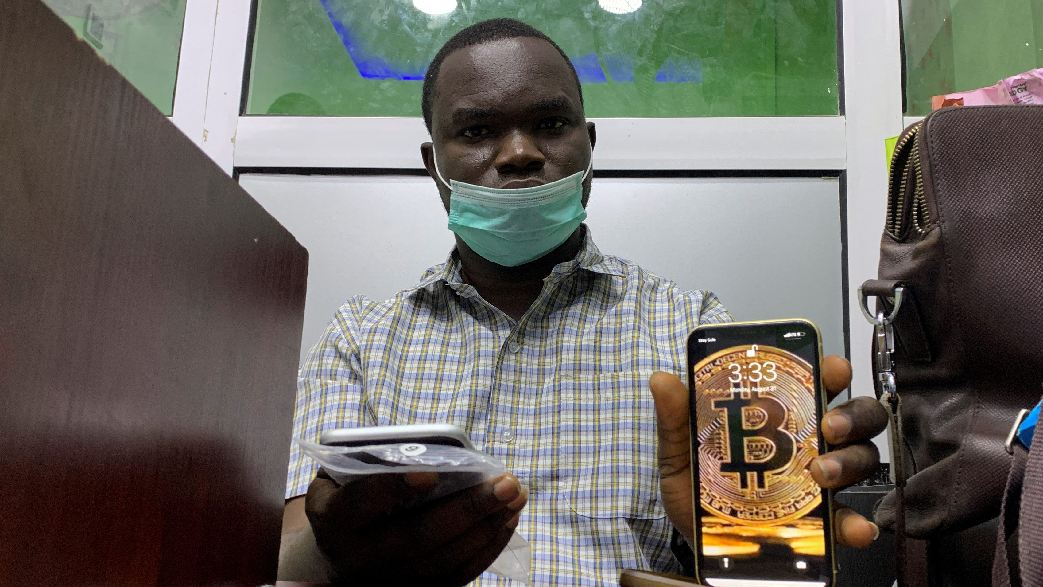 An image of a man posing with a phone that shows a bitcoin-inspired wallpaper