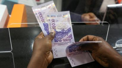 An image of a woman counting bank notes in Abidjan, Ivory Coast