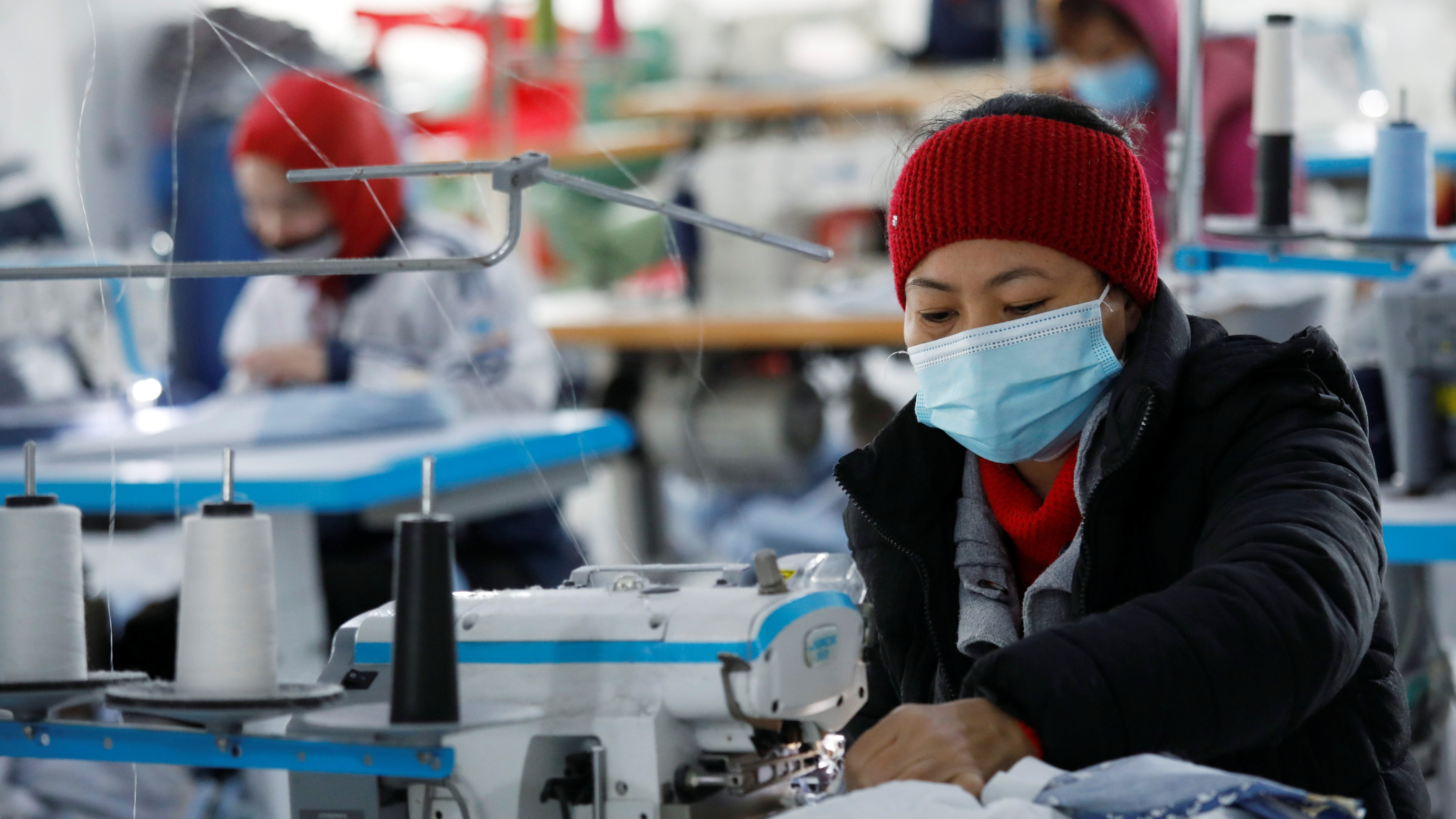 A woman wearing a surgical mask sits at a sewing machine in a Vietnamese factory.
