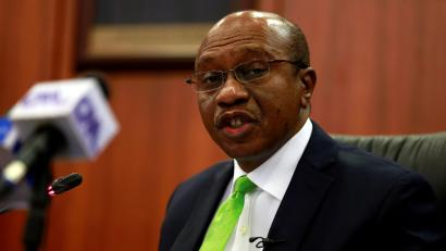 A picture of Nigeria's central bank governor Godwin Emefiele speaking about something, while wearing a black suit, white shirt and a very on-brand lemon-green tie