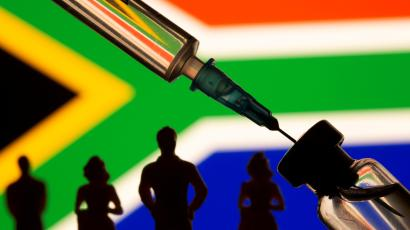 Illustration of a vial and syringe by a South African flag