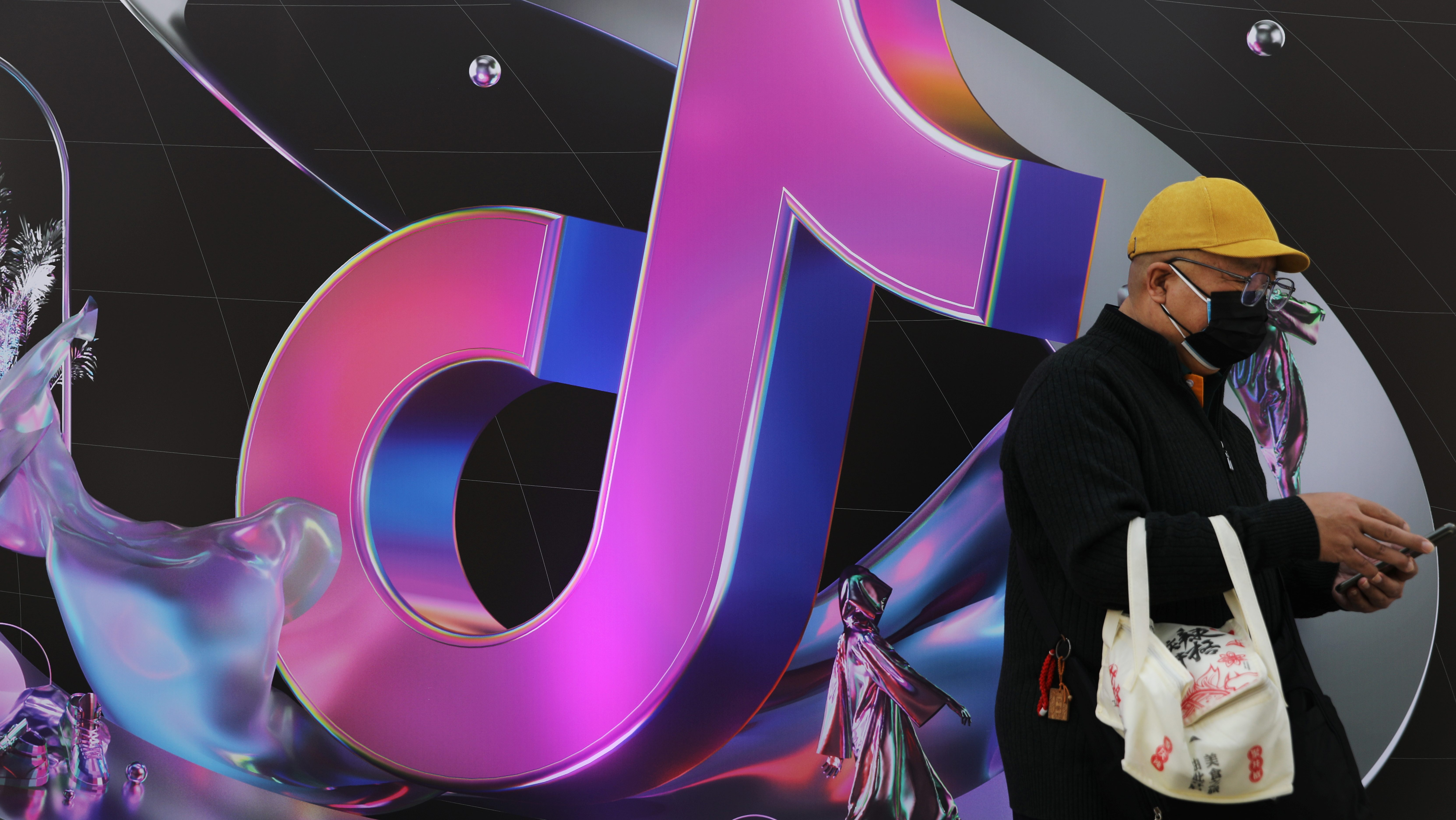 Man stands near a giant sign of Chinese company ByteDance's app TikTok, known locally as Douyin, during China Fashion Week, in Beijing