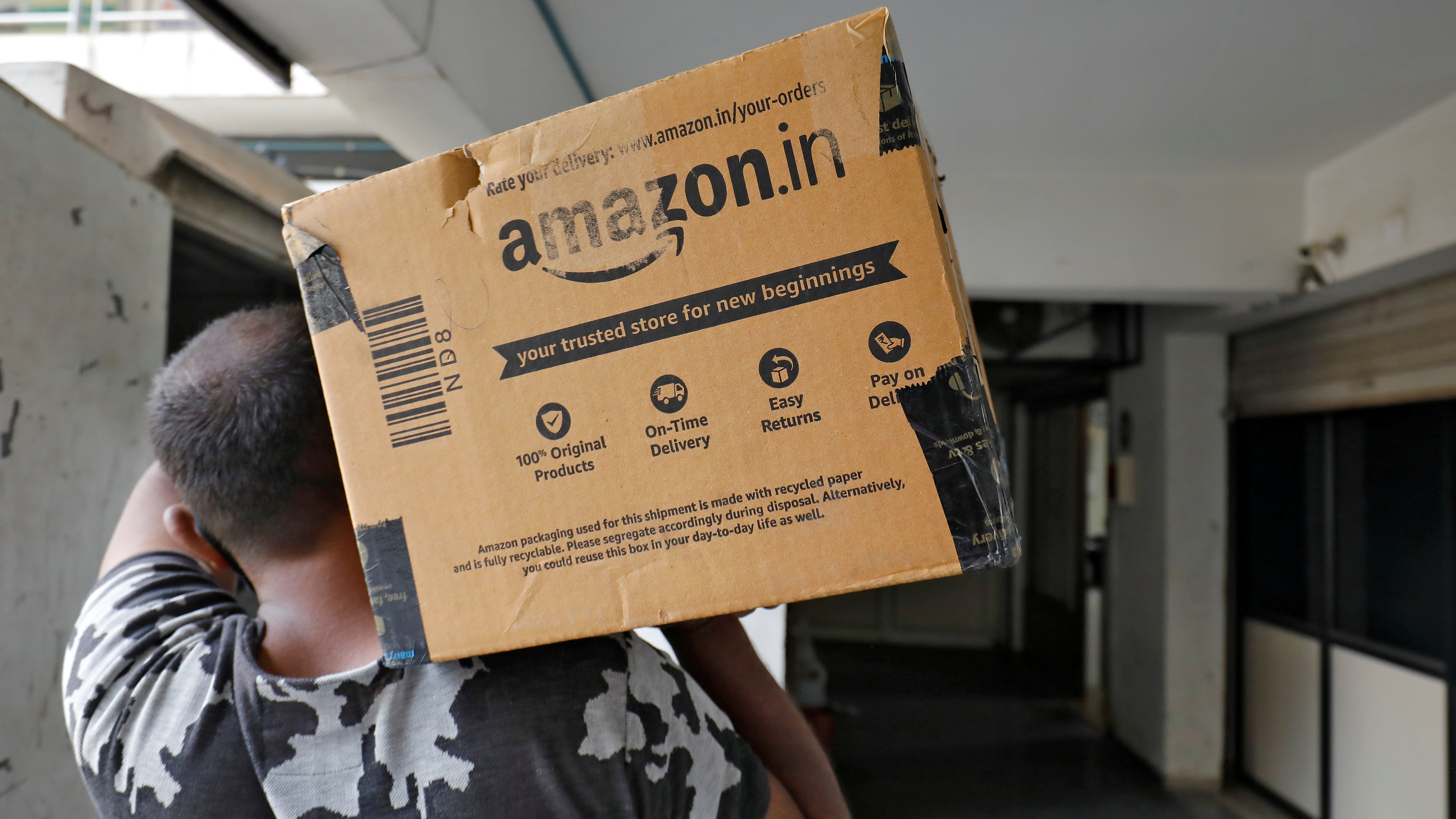 FILE PHOTO: A delivery worker of Amazon carries a packet to deliver it to a customer at a residential apartment in Ahmedabad
