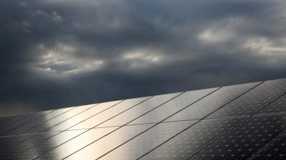 The sun is reflected on solar panels which produce renewable energy