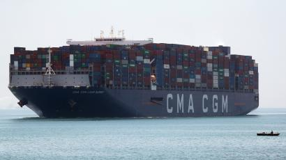 A fisherman travels on a boat in front of a CMA CGM container ship passing through the Suez Canal.