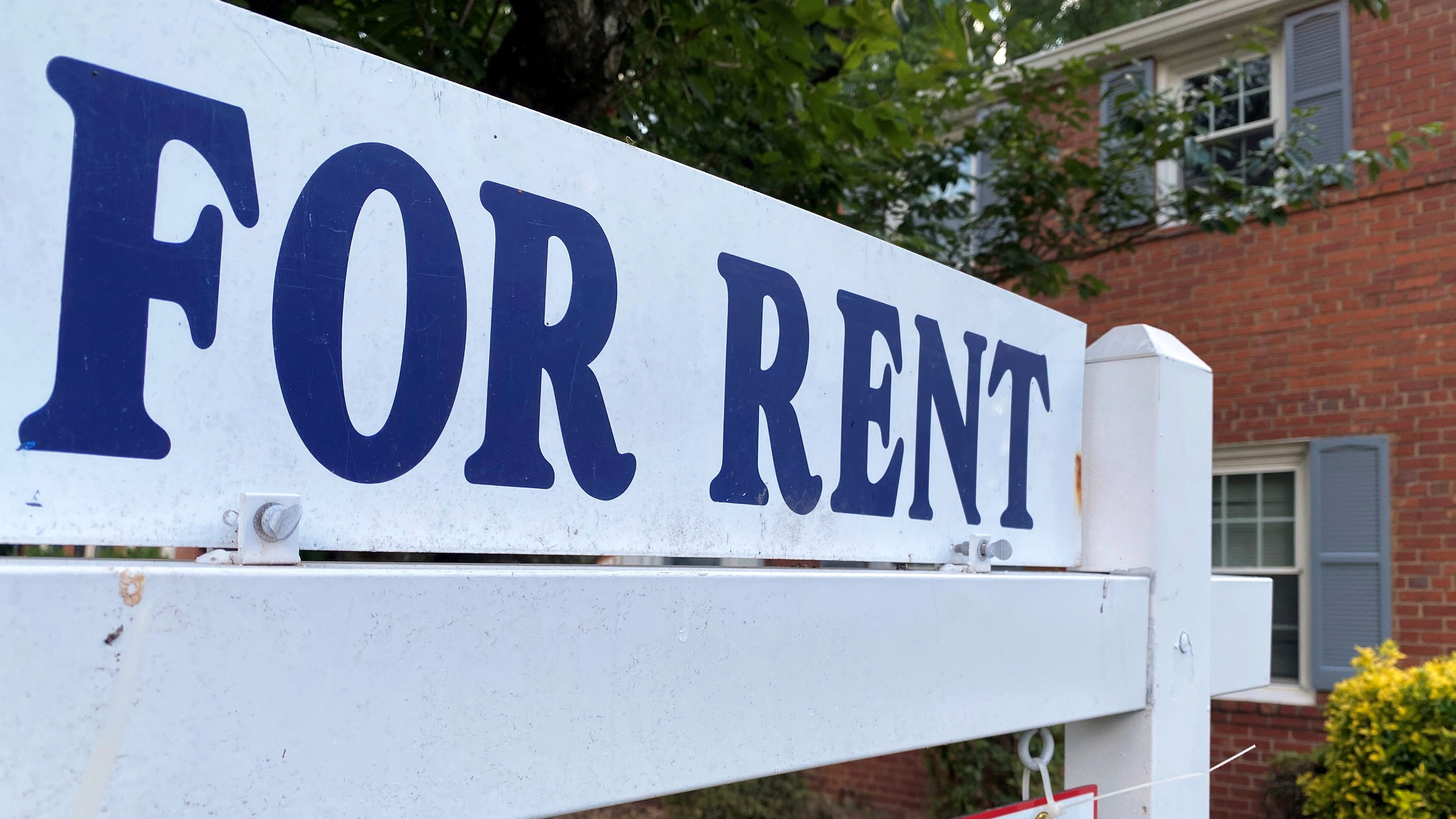 A white sign reads FOR RENT in blue text in front of a brick house