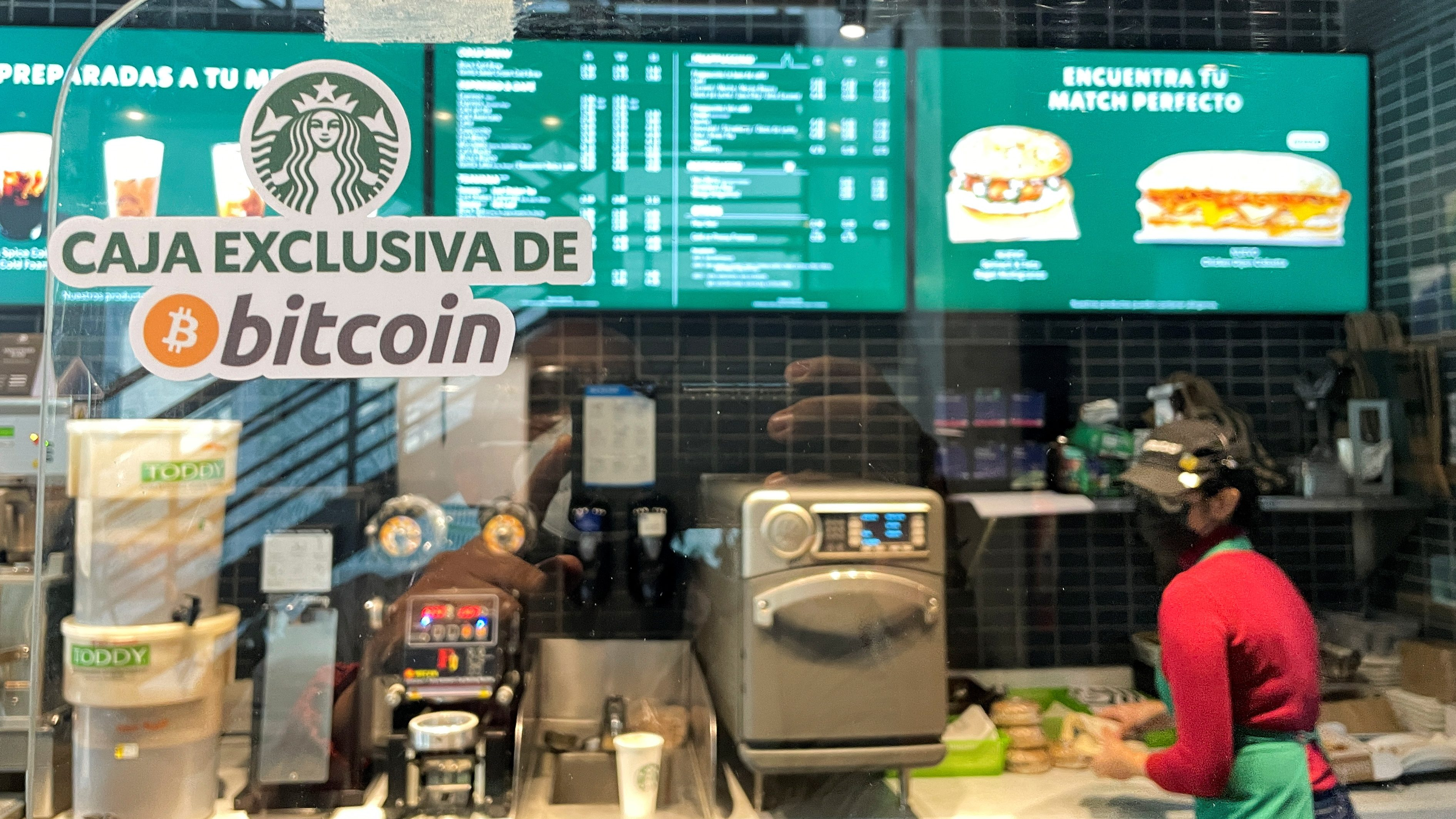 """A sign reads: """"Exclusive Bitcoin register"""" in a Starbucks store where the cryptocurrency is accepted as a payment method, in El Salvador"""