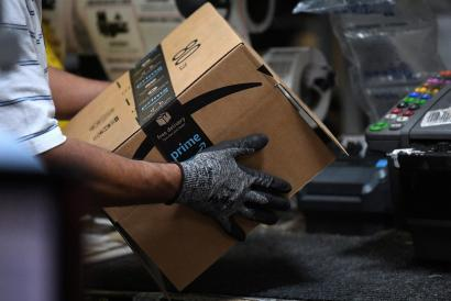 Worker assembles a box for delivery at the Amazon fulfilment center in Baltimore