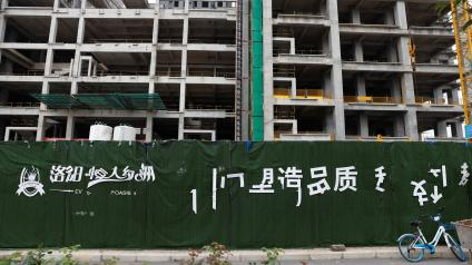 A peeling logo of the Evergrande Oasis, a housing complex developed by Evergrande Group, is seen outside the construction site where the residential buildings stand unfinished, in Luoyang, China September 16, 2021. Picture taken September 16, 2021.
