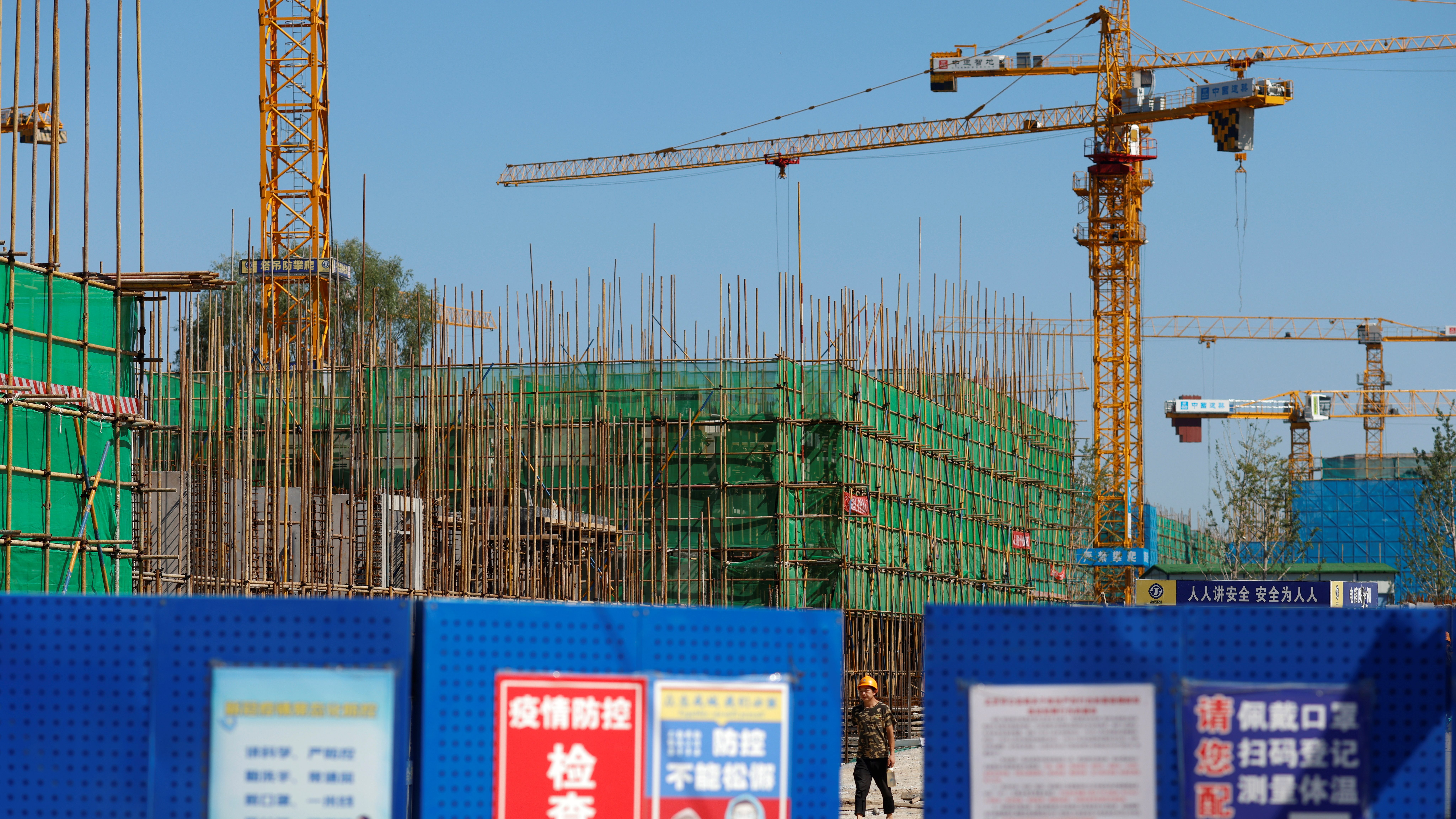A worker walks inside the construction site of a project developed by China Evergrande Group in Beijing, China