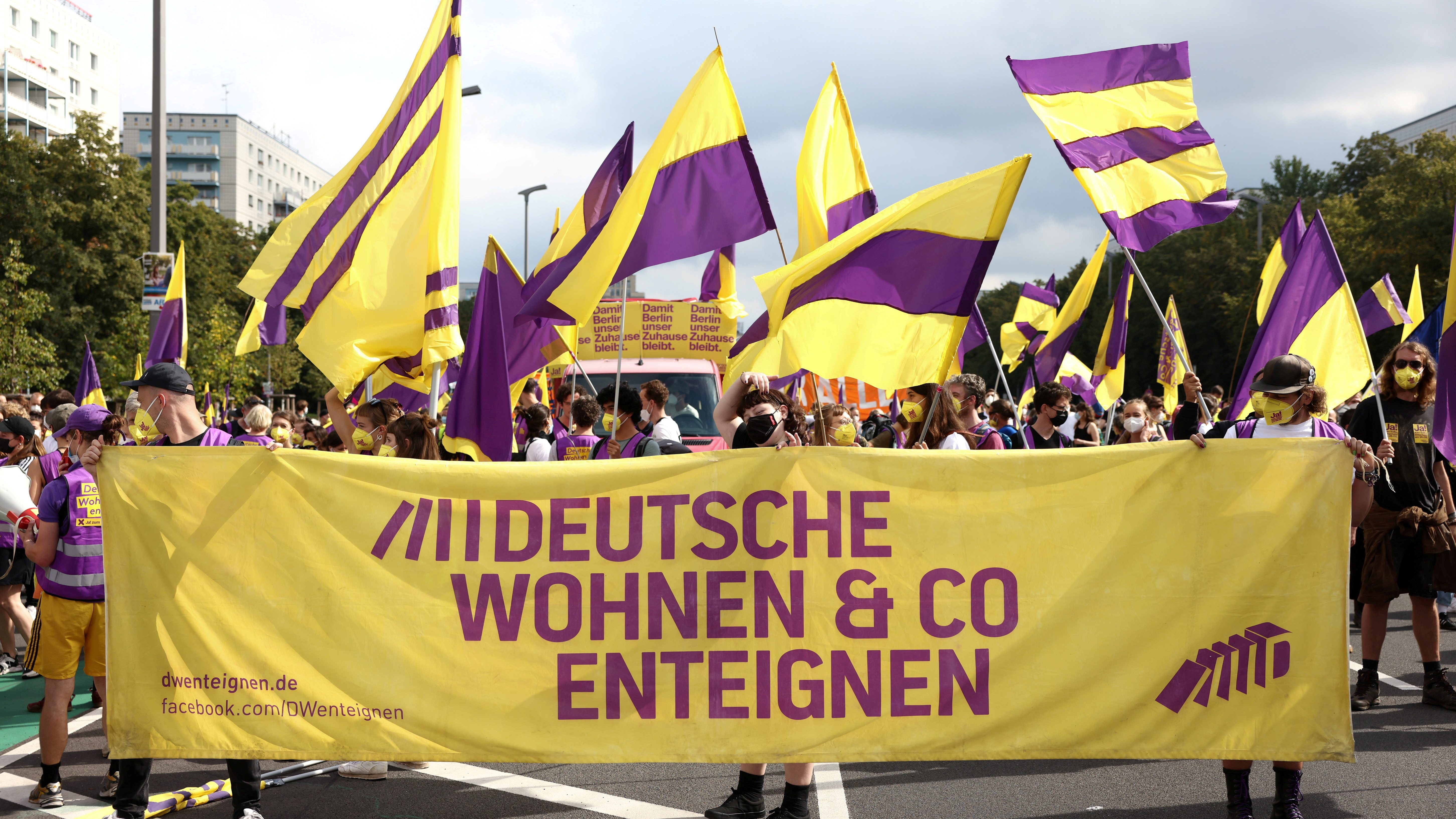 people marching waving yellow and purple flags, and holding a yellow banner with purple text written in German