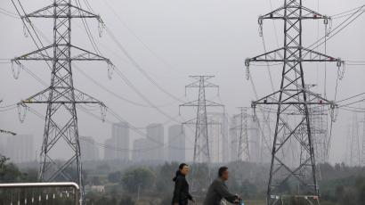People walk past electricity pylons in Shenyang, Liaoning province, China.