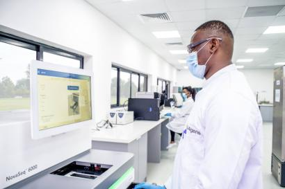 A picture of a man in a lab, wearing a white coat and a nose mask, facing a screen.