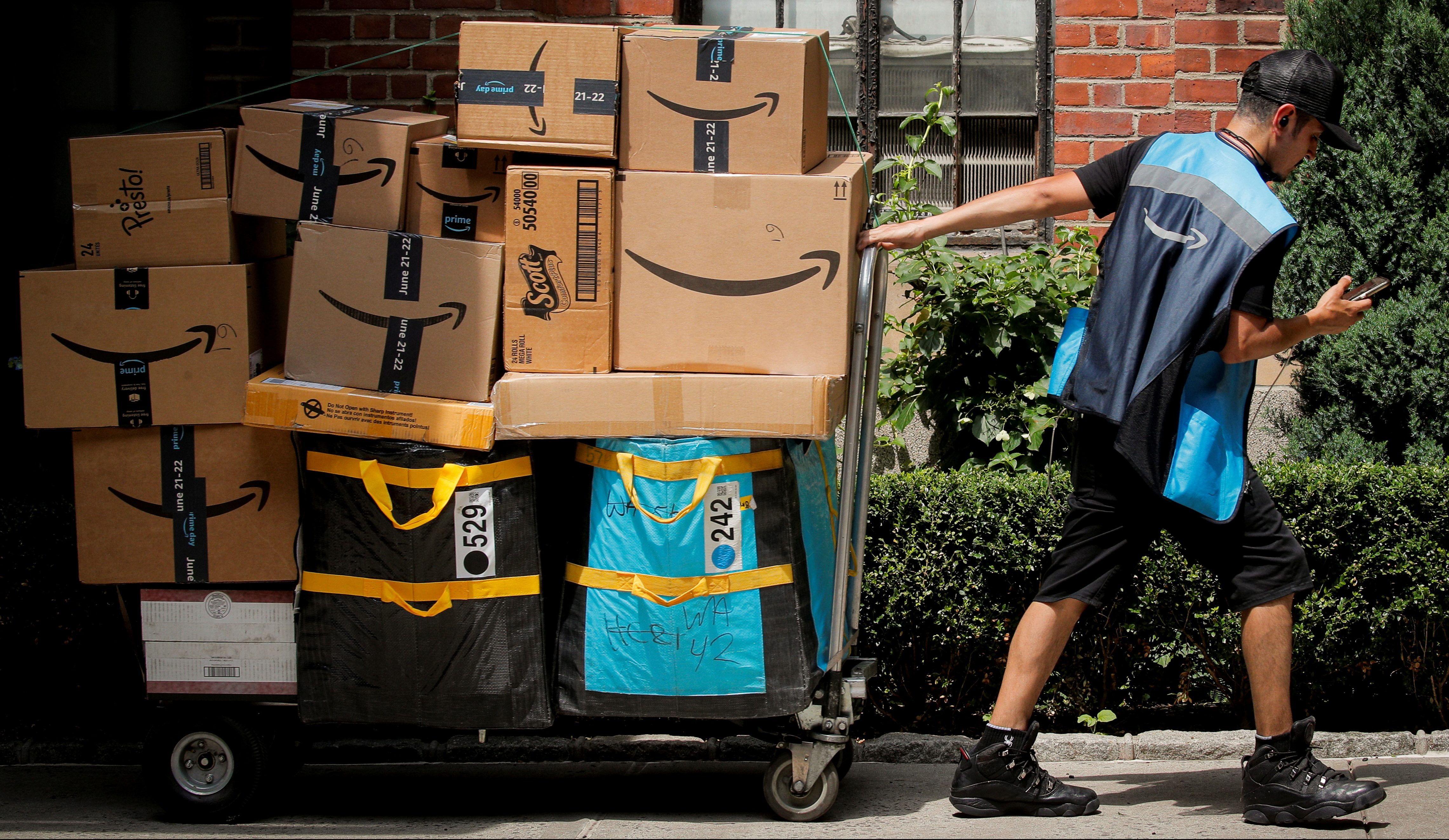 An Amazon delivery worker pulls a delivery cart full of packages