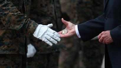 U.S. President Joe Biden hands challenge coins to members of the U.S. Marine Corps Honor Guard before boarding Air Force One at Dover Air Force Base in Dover, Delaware, U.S.