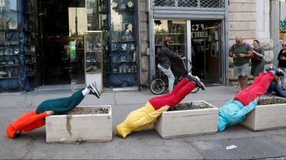 """Three dancers face down on the pavement with their feet elevated on sidewalk planters in """"Bodies in Urban Spaces"""" event"""